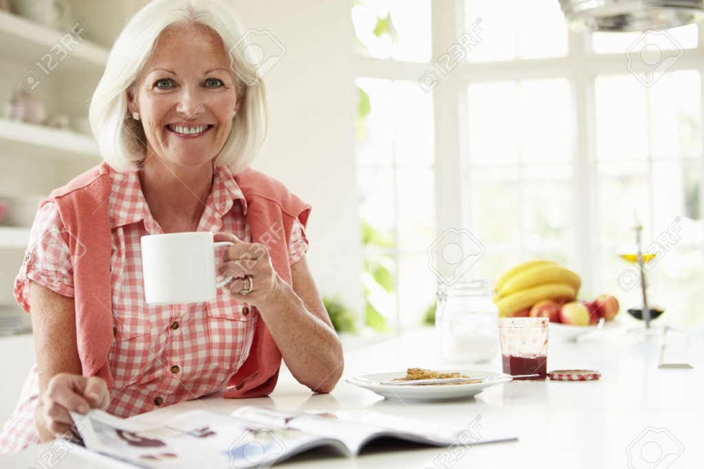 31003421-Middle-Aged-Woman-Reading-Magazine-Over-Breakfast-Stock-Photo